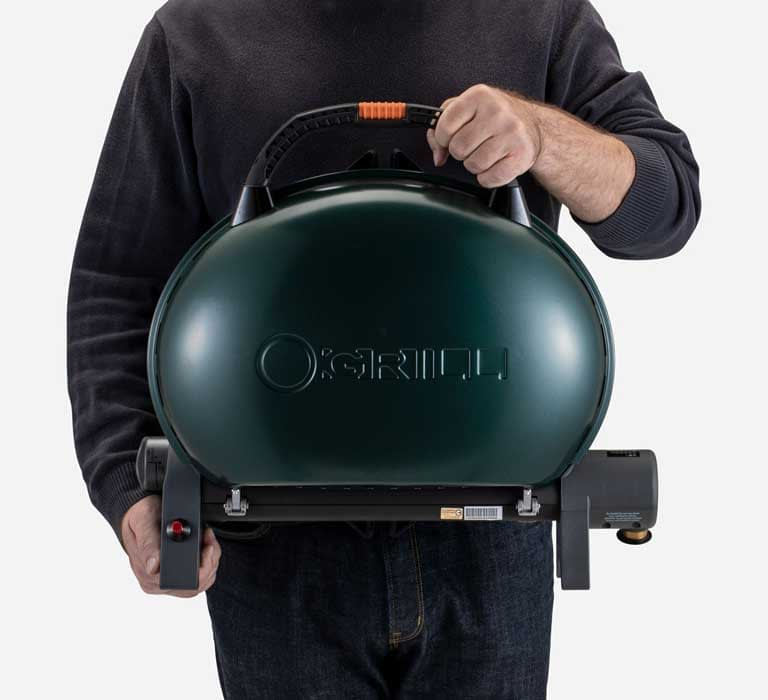 A person is holding O-Grill 500M Portable Gas Grill