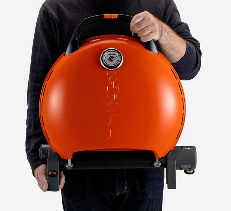 A person is holding O-Grill 600MT Portable Gas Grill