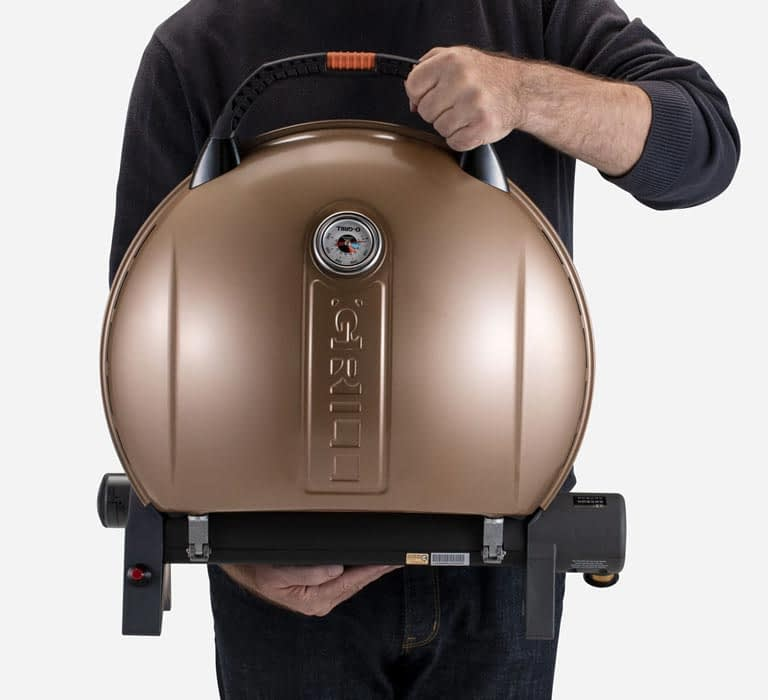 A person is holding O-Grill 900MT Portable Gas Grill